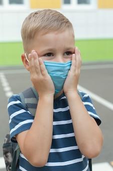 Piccolo scolaro biondo che indossa la maschera durante l'epidemia di virus corona