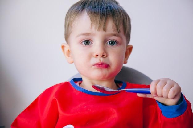 Piccolo bambino caucasico biondo che mangia a casa. stile di vita familiare e dietetico.