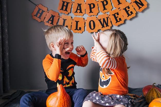 Una bambina bionda e un ragazzo in costume da zucca per halloween, dolcetto o scherzetto, i bambini festeggiano halloween. pronto per la vacanza dolcetto o scherzetto