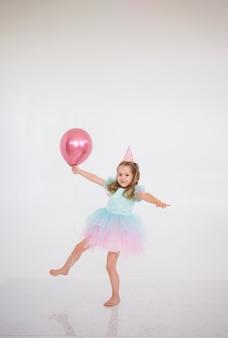 Una bambina bionda in un vestito elegante balla con un palloncino rosa su uno sfondo bianco con un posto per il testo