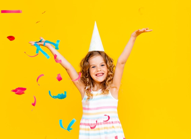 La piccola ragazza bionda con un berretto festivo e un vestito bianco cattura i coriandoli un sorriso felice su uno sfondo giallo.