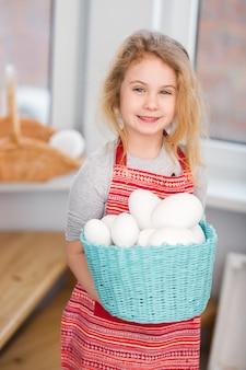 Cestino della holding della piccola ragazza bionda con le uova dipinte. pasqua.
