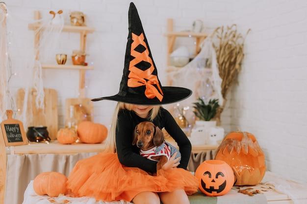Bimba bionda tiene un bassotto nano in grembo su uno sfondo di zucche halloween