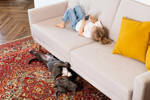 Una bimba bionda a casa sul divano con un cellulare e un grosso cane, bambini e gadget.