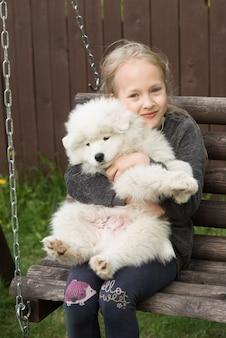 Bambina bionda che abbraccia un cucciolo samoiedo nel parco