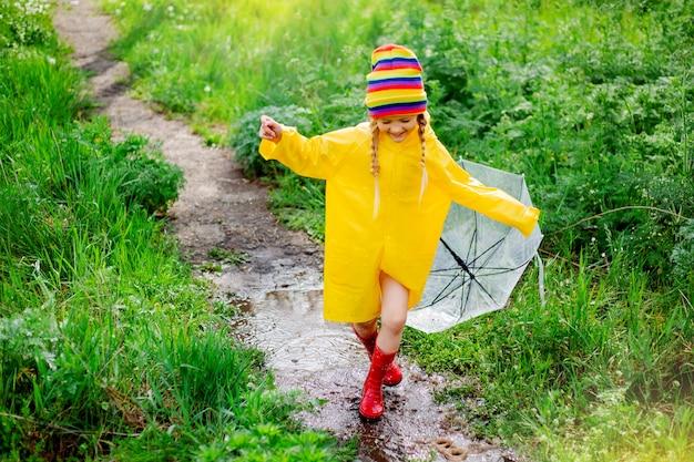 La piccola ragazza bionda sorride salta sulle pozzanghere in primavera in impermeabile giallo e stivali di gomma con l'ombrello