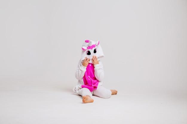 Piccola ragazza bionda che sorride nel kigurumi su spazio bianco