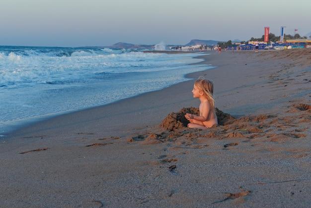 Una piccola ragazza bionda in costume da bagno si siede su una spiaggia sabbiosa in riva al mare e gioca con la sabbia a