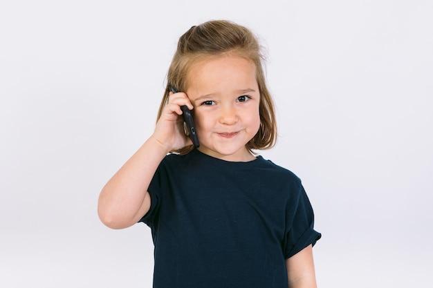 Piccola ragazza bionda che parla sul suo telefono cellulare