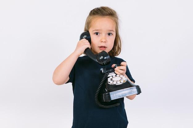 Piccola ragazza bionda che parla sul suo telefono retrò