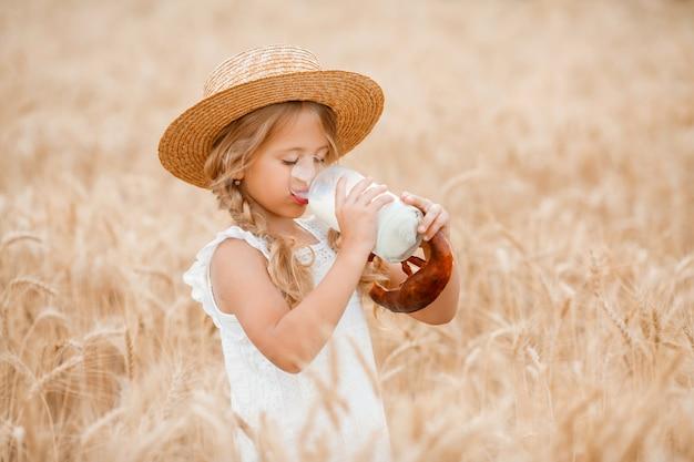 La piccola ragazza bionda nel campo di grano mangia il pane e beve il latte