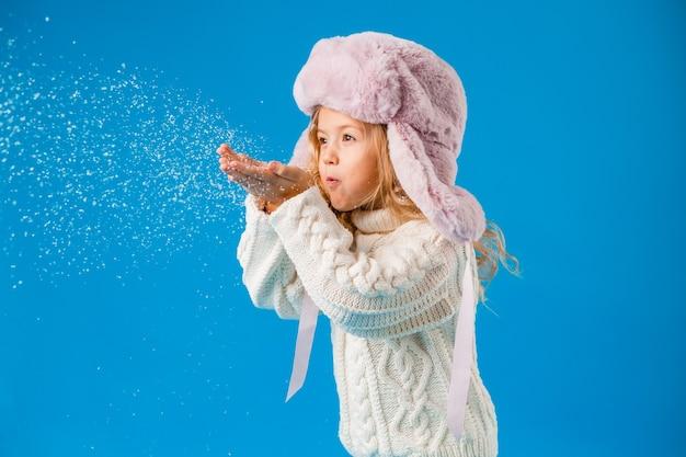 Piccola ragazza bionda in abiti invernali soffia la neve dalle sue mani