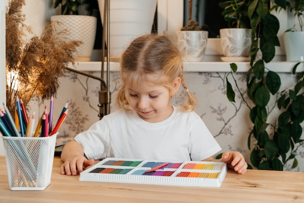 Una bambina bionda con una tavolozza di colori vivaci di plastilina colorata per modellare al tavolo