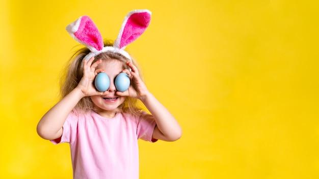 Una bambina bionda con le orecchie del coniglietto di pasqua e le uova colorate di pasqua su uno sfondo giallo con spazio per il testo.