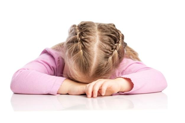 La piccola ragazza bionda con le trecce si trova al tavolo. isolato su sfondo bianco.