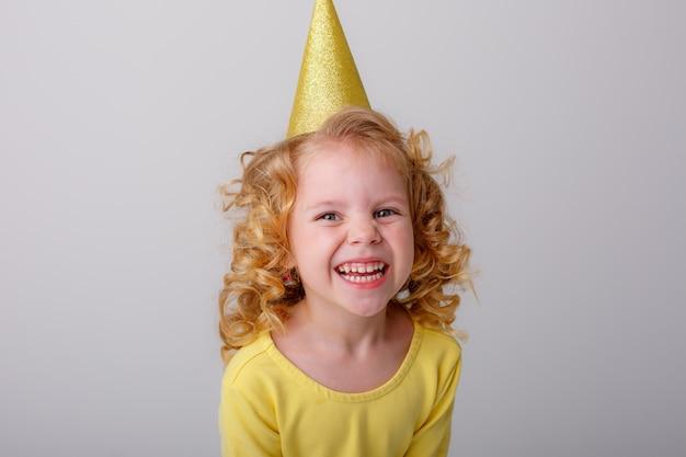 Bambina bionda in un vestito giallo con una sorpresa di compleanno del cappello su uno spazio bianco