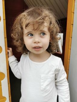 Bambina dagli occhi azzurri che guarda sospettosamente di lato lasciando una casa delle bambole.