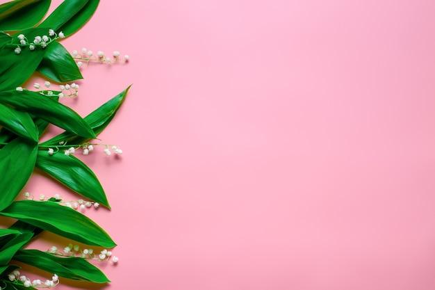 Piccoli bouquet e foglie verdi di mughetto come bordo floreale a sinistra con copia spa...