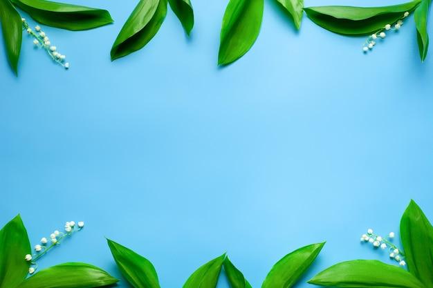 Piccoli mazzi di mughetto con bordi floreali sullo spazio della copia distesi con retro blu...