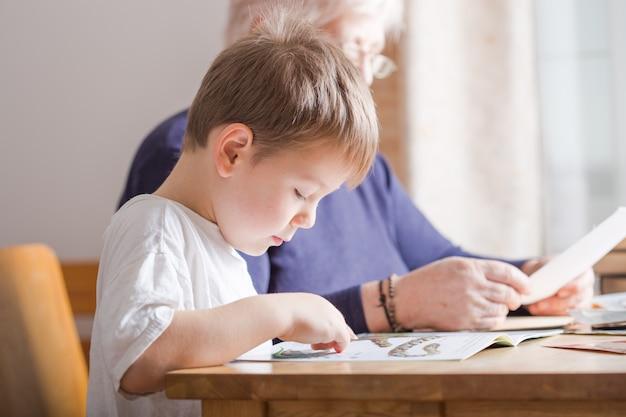 Libro di lettura di 4 anni del ragazzino. è seduto su una sedia nel soleggiato soggiorno a guardare le foto nella storia. kid facendo i compiti per la scuola elementare o la scuola materna. i bambini studiano.