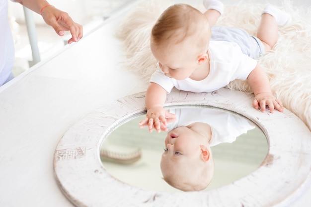 Il bambino di 7 mesi gioca sul tappeto bianco in camera da letto con uno specchio