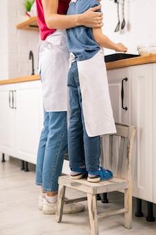 Ragazzino in grembiule in piedi sulla sedia squallida dal tavolo della cucina mentre aiuta la sua mamma con la cottura del cibo