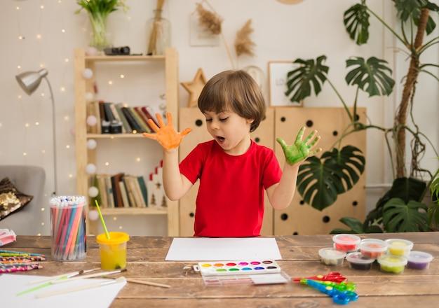 Un piccolo artista con le palme dipinte si siede a un tavolo nella stanza