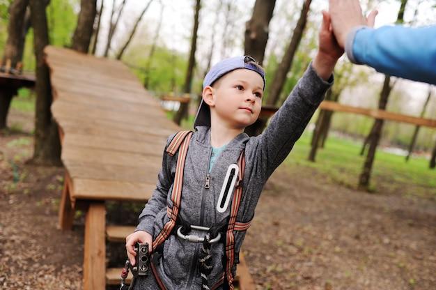 Un bambino su un'attrazione in un parco di corde passa una corsa ad ostacoli