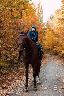Un ragazzino con una giacca blu sta andando a cavallo in un parco autunnale