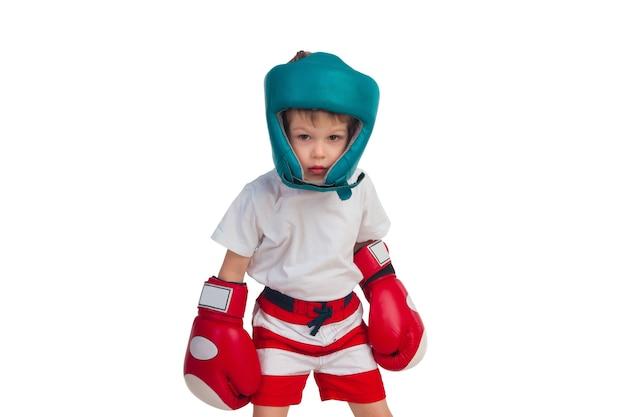 Ragazzino in guantoni da boxe e un casco su una superficie bianca