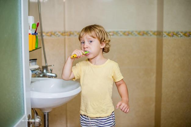 Ragazzino che pulisce i suoi denti nel bagno