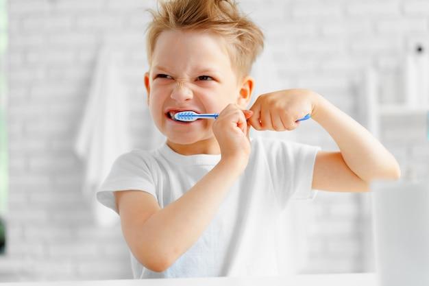 Ragazzino che pulisce diligentemente i suoi denti in bagno