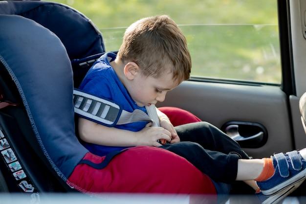 Il ragazzino allacciato con la cintura di sicurezza all'interno dell'auto. concetto di veicolo e trasporto.