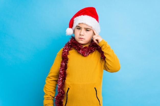 Il ragazzino che celebra il giorno di natale che porta un cappello di santa ha isolato il tempio indicante con il dito, pensando, si è concentrato su un compito.