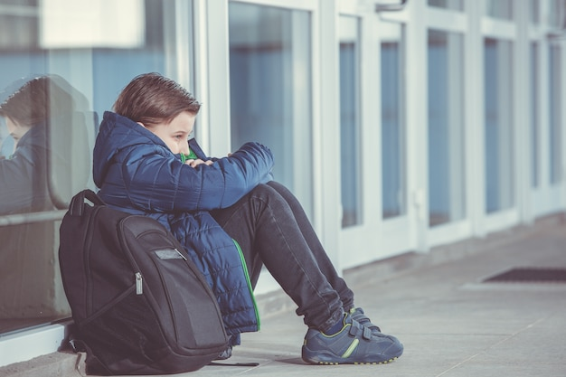 Ragazzino o bambino seduto da solo sul pavimento davanti alla scuola dopo aver subito un atto di bullismo