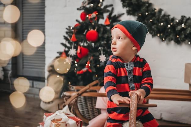 Un ragazzino in costume da elfo di natale si siede su un cavallo di legno e guarda di lato il bokeh in una stanza con decorazioni natalizie di capodanno.