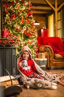 Un ragazzino in pigiama di natale si siede vicino a un albero di natale