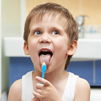 Il ragazzino pulisce la lingua con uno spazzolino da denti
