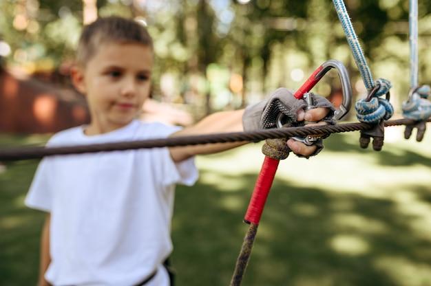 Il ragazzino si arrampica nel parco delle funi, scalatore