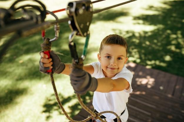 Il ragazzino si arrampica nel parco delle funi
