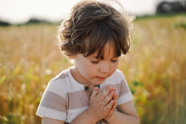 Little boy chiuse gli occhi, pregando in un campo di grano. mani giunte in preghiera. foto di alta qualità