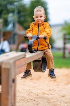 Little boy confuso su altalena altalena primo giorno nel parco giochi