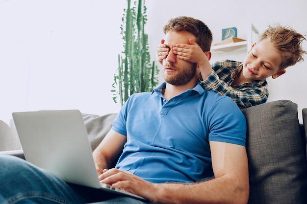 Il ragazzino copre gli occhi del padre con le mani nel soggiorno di casa