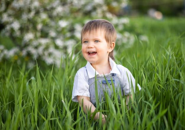 Un ragazzino in salopette di jeans con gli occhi azzurri espressivi. saltare e scherzare nell'erba alta e verde sullo sfondo di un grande cespuglio verde e di un giardino fiorito.