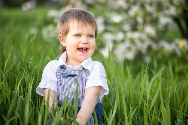 Un ragazzino in salopette di jeans con occhi azzurri espressivi. saltare e scherzare nell'alta erba verde contro