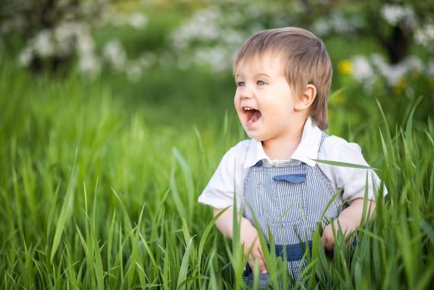 Un ragazzino in salopette di jeans con occhi azzurri espressivi. saltare e scherzare nell'erba alta e verde