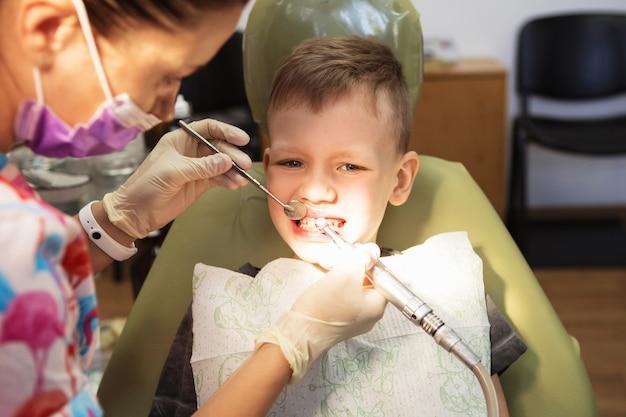 Un ragazzino al ricevimento di un dentista in una clinica odontoiatrica. odontoiatria pediatrica, odontoiatria pediatrica.