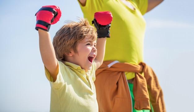 Ragazzino che fa esercizio di boxe con il nonno. il padre sta allenando il figlio di boxe. ragazzino sportivo alla formazione di boxe con l'allenatore. uomo di sport coaching boxe ragazzino in guantoni da boxe rossi.