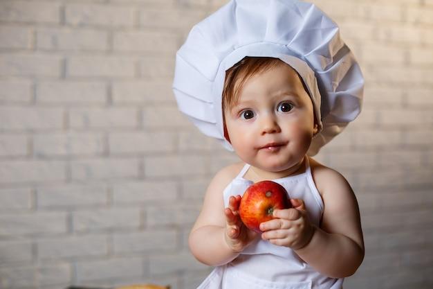 Ragazzino vestito da cuoco in cucina. bel bambino vestito con un grembiule che mangia una mela
