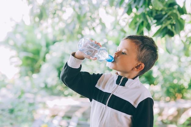 Un ragazzino beve acqua all'aperto da una bottiglia blu